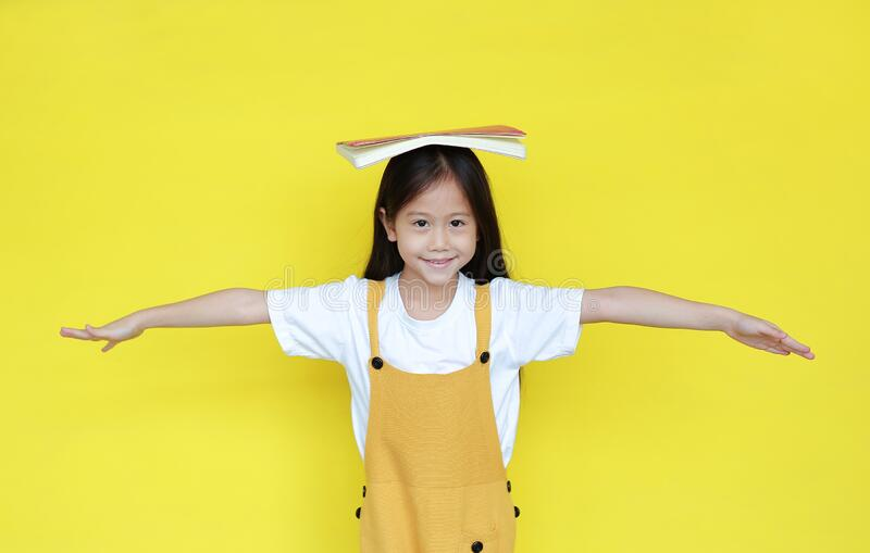 Asian child girl with book on head isolated on yellow background. Portrait of happy schoolgirl open arms wide and looking at stock images