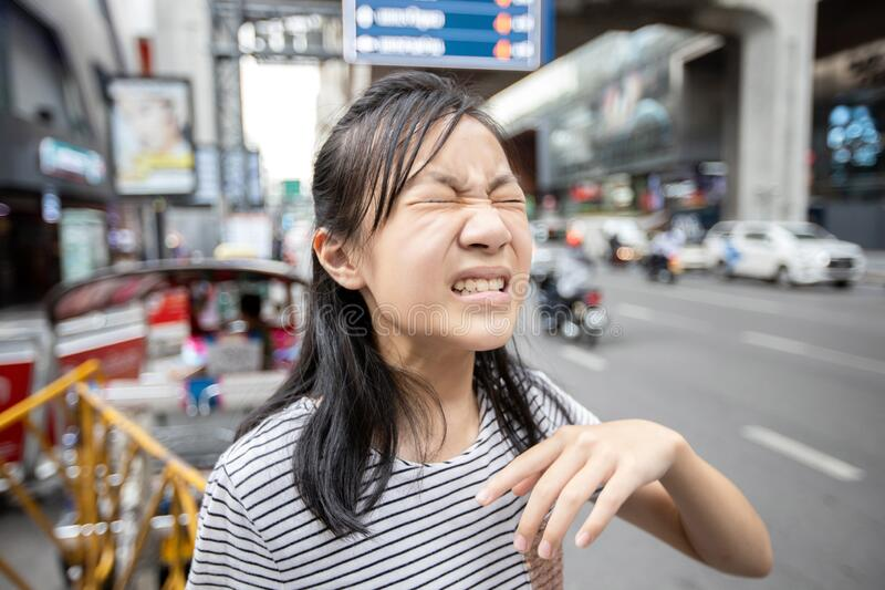 Asian child girl with a burning sensation,eye irritation from car smoke in the city,feel eyes pain,dust,ocular allergy with closed. Eyes effect of air pollution royalty free stock image