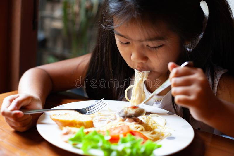 Asian child girl eating delicious Spaghetti Carbonara royalty free stock images