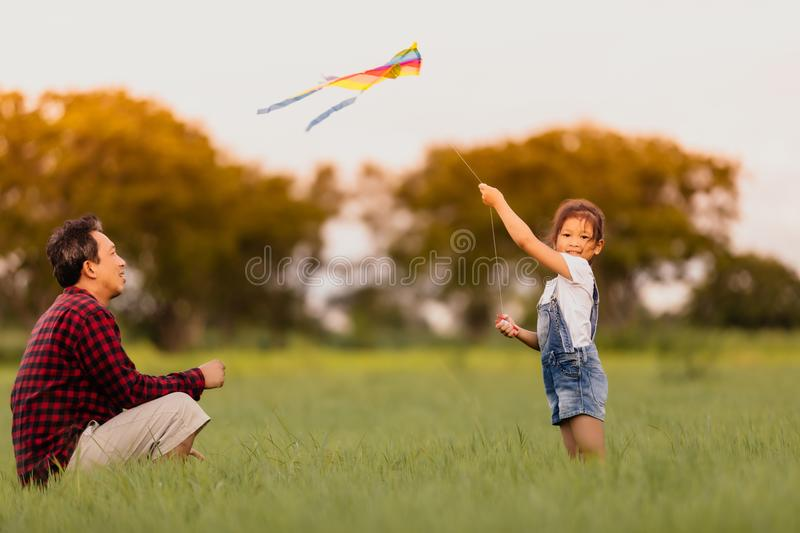 Asian child girl and father with a kite running and happy on meadow in summer in nature stock photo