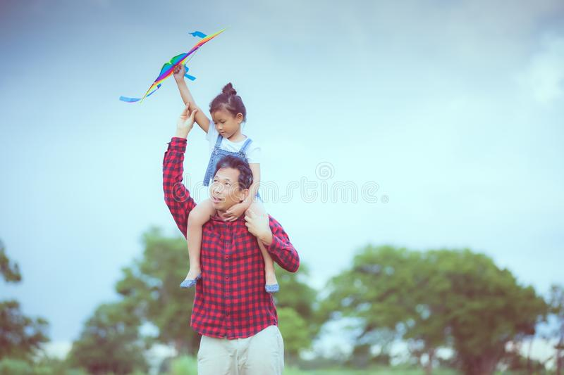 Asian child girl and father with a kite running and happy on meadow in summer in nature stock images