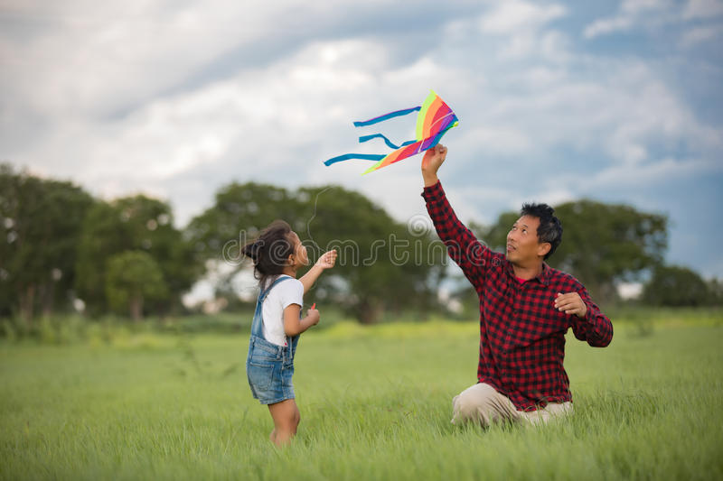 Asian child girl and father with a kite running and happy on meadow in summer in nature royalty free stock images
