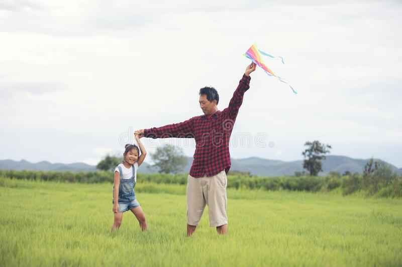 Asian child girl and father with a kite running and happy on meadow in summer in nature stock photography