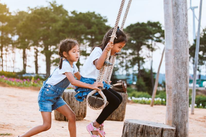 Asian child girl having fun to play on wooden swings with her sister in playground with beautiful nature stock images