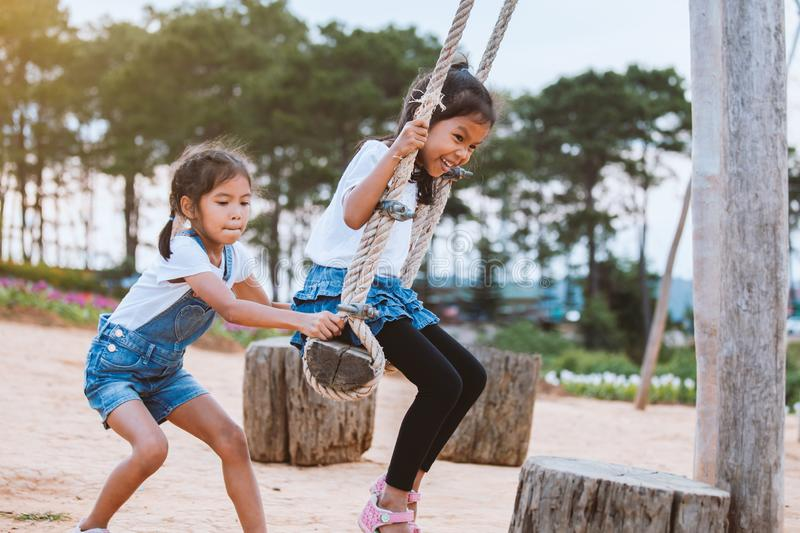 Asian child girl having fun to play on wooden swings with her sister in playground with beautiful nature royalty free stock images