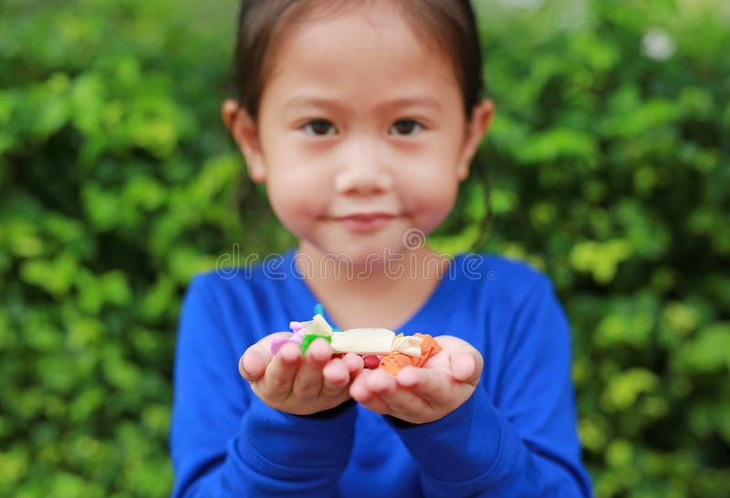 Asian child girl holding some thai sugar and fruit toffee with colorful paper wrapped in her hands. Focus at candy in her hands.  royalty free stock photo
