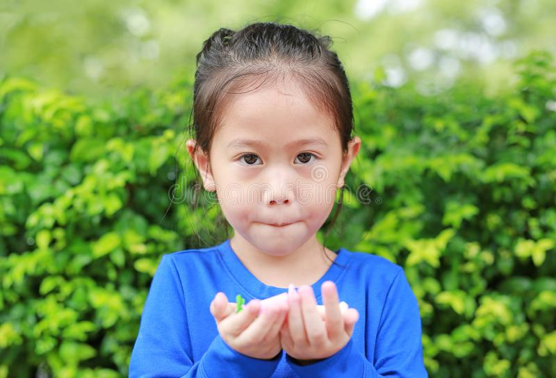 Asian child girl holding some thai sugar and fruit toffee with colorful paper wrapped in her hands. Focus at candy in her hands stock image