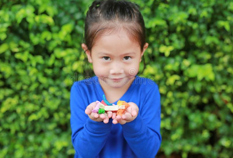 Asian child girl holding some thai sugar and fruit toffee with colorful paper wrapped in her hands. Focus at candy in her hands.  royalty free stock image