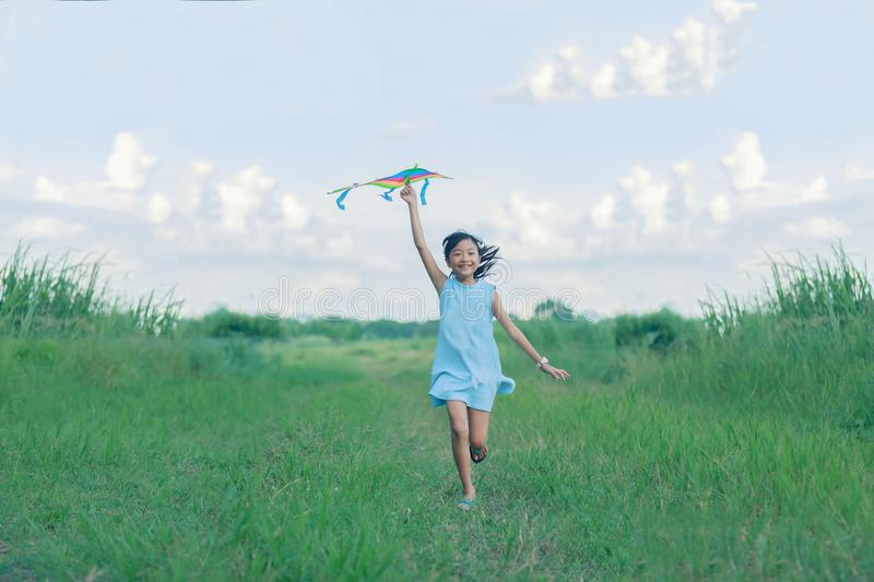 Asian child girl with a kite running and happy on meadow in summer in nature royalty free stock image