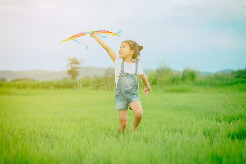 Asian child girl with a kite running and happy on meadow in summer in nature royalty free stock images