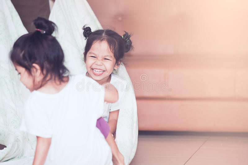 Asian child girl laughing and having fun to play with blanket. Happy asian child girl laughing and having fun to play with blanket and sister in the house in royalty free stock image
