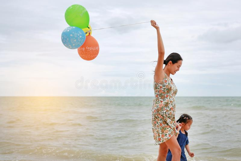 Asian child girl and mother on the beach with colorful balloons. Holiday concept royalty free stock photography