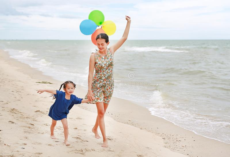 Asian child girl and mother on the beach with colorful balloons. Holiday concept royalty free stock photo