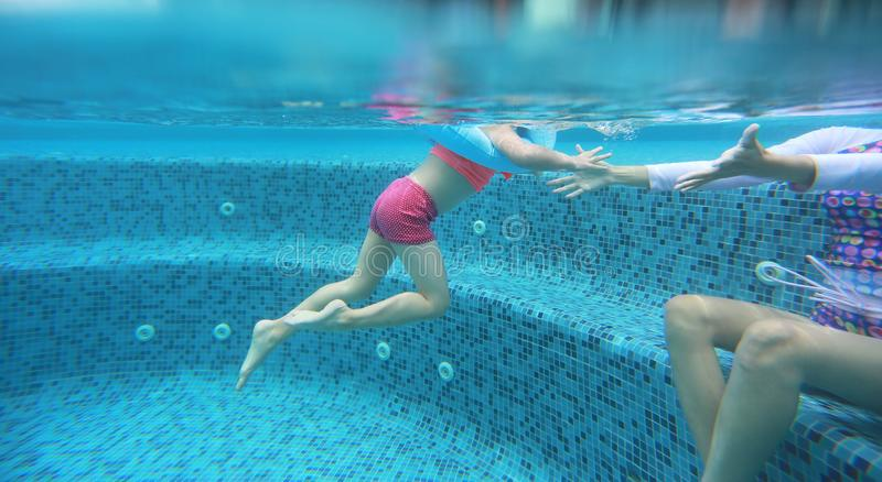 Asian child girl with mother in swimming underwater in the pool stock image