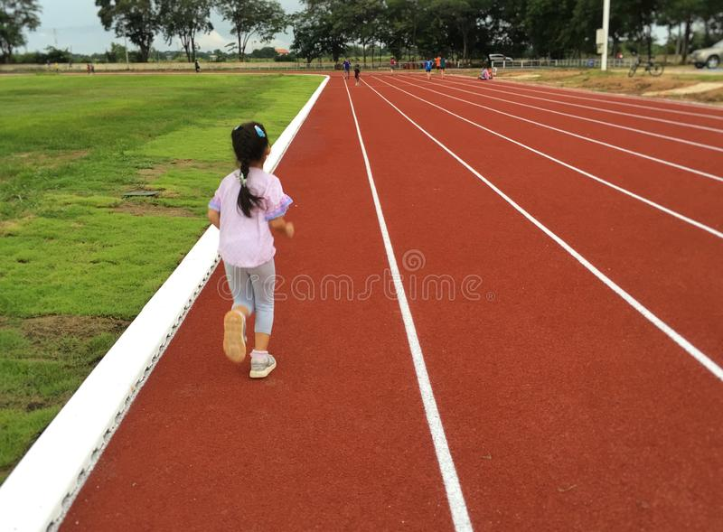 Asian child girl running on red track. stock image