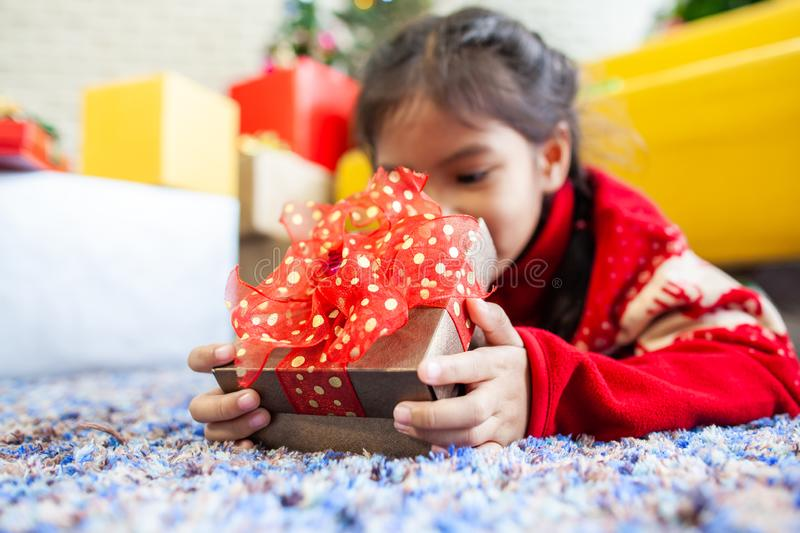 Asian child girl surprise with gift and holding beautiful gift box in hand on Christmas celebration. Cute asian child girl surprise with gift and holding royalty free stock photos