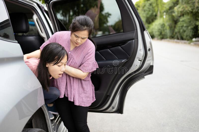Asian child girl about to throw up from car sick or indigestion,female teenage vomiting in a car suffers from motion sickness,. Daughter feeling dizzy from royalty free stock photo