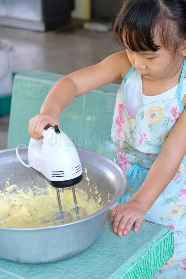Asian child girl is using an electric beater to beat the dough to make pastries. stock photos
