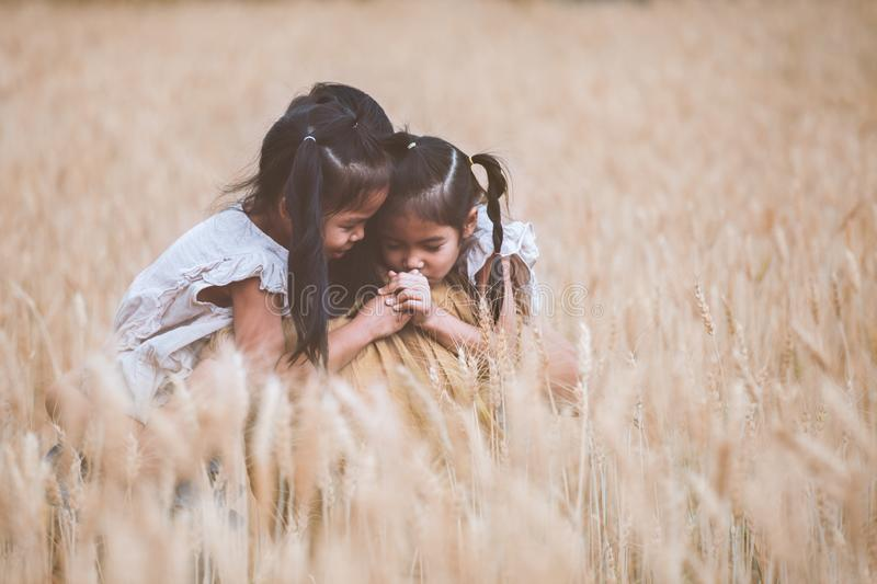 Asian child girls hugging their mother and having fun to play with mother in the barley field in vintage color tone. Happy asian child girls hugging their mother royalty free stock photo