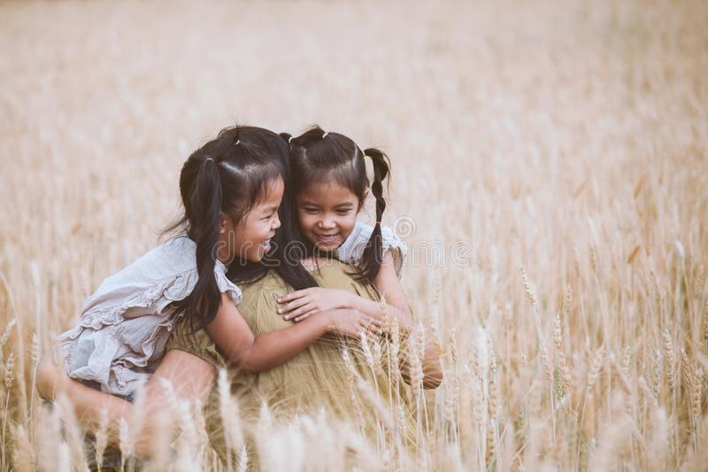Asian child girls hugging their mother and having fun to play with mother in the barley field in vintage color tone. Happy asian child girls hugging their mother stock photos