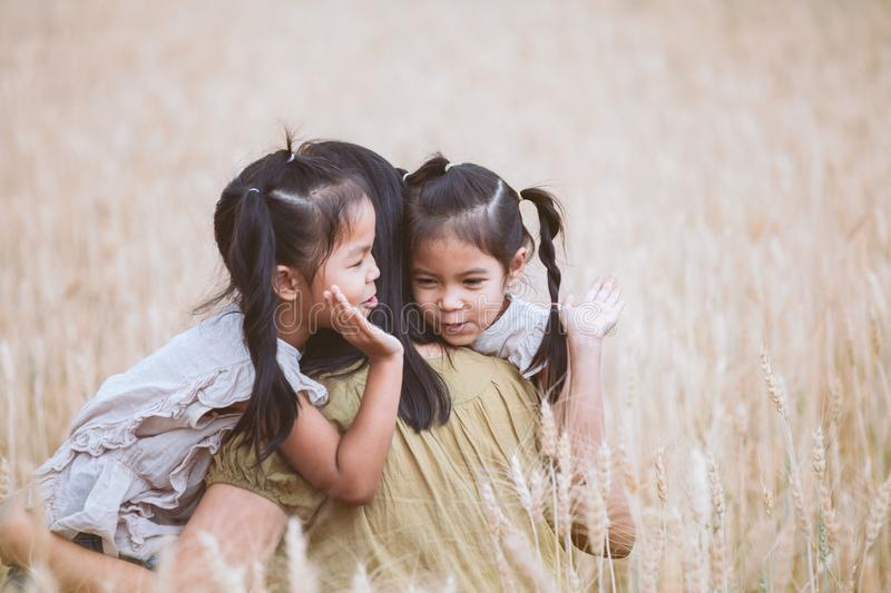 Asian child girls hugging their mother and having fun to play with mother in the barley field in vintage color tone. Happy asian child girls hugging their mother royalty free stock image