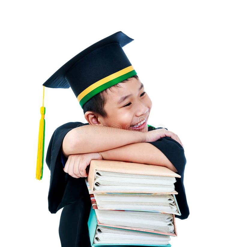 Asian child in graduation gown with many books. Isolated on whit royalty free stock image