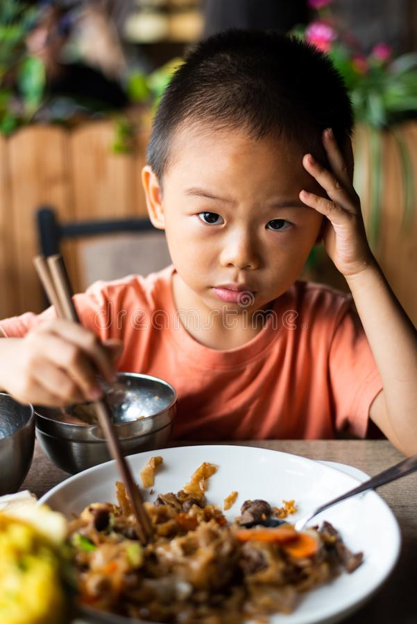 Asian child having lunch at the restaurant royalty free stock photos