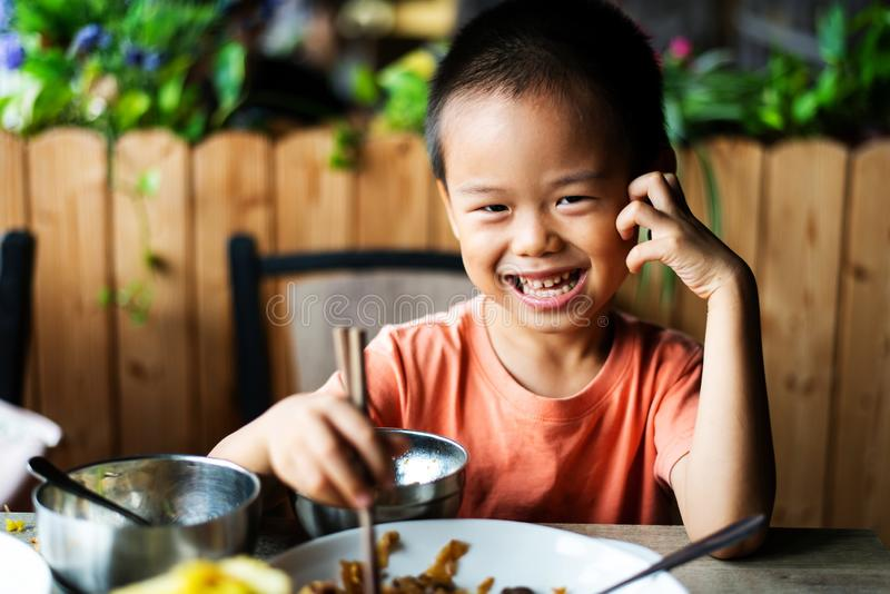 Asian child having lunch at the restaurant. Cute Asian child having lunch at the restaurant, eating, kid, food, small, thai, chinese, chopsticks, 4, meal stock photography