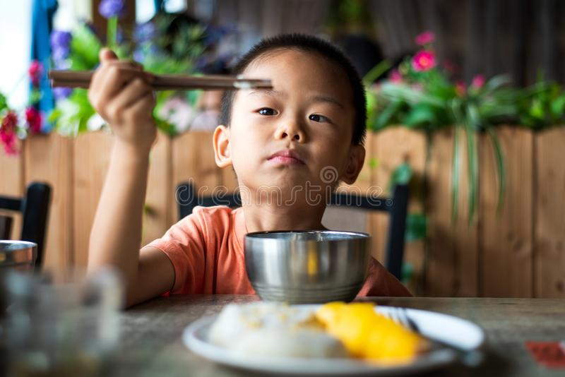 Asian child having lunch at the restaurant. Cute Asian child having lunch at the restaurant, eating, kid, food, small, thai, chinese, chopsticks, 5, look stock photo