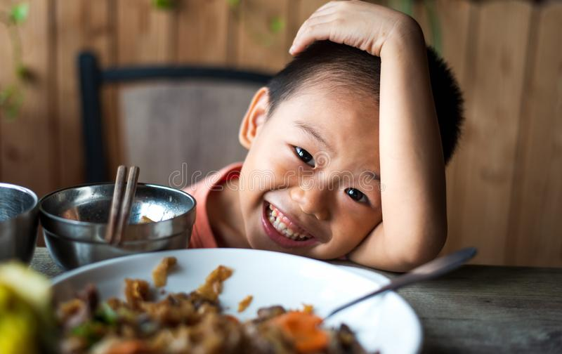 Asian child having lunch at the restaurant. Cute Asian child having lunch at the restaurant, eating, kid, food, small, thai, chinese, chopsticks, 4, meal stock image
