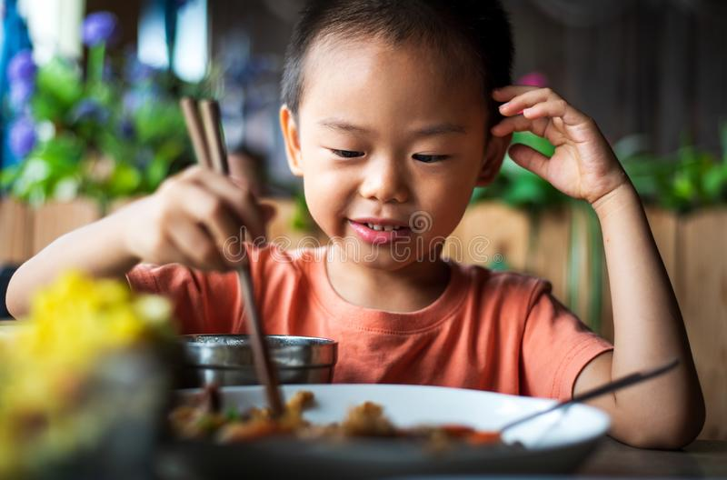 Asian child having lunch at the restaurant. Cute Asian child having lunch at the restaurant, eating, kid, food, small, thai, chinese, chopsticks, 4, meal stock images