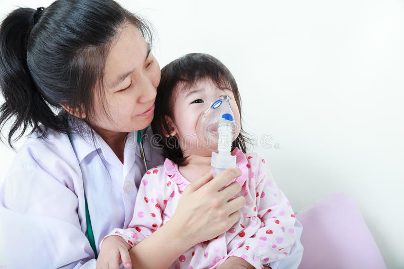 Asian child having respiratory illness helped by health professional with inhaler. Sad girl crying. royalty free stock image