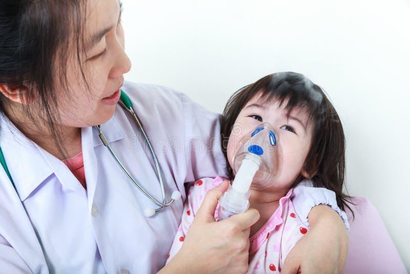 Asian child having respiratory illness with inhaler. Sad girl cr stock image