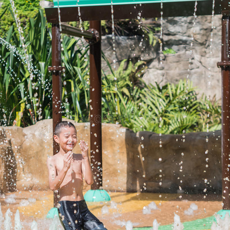 Asian child little boy having fun to play with water in park fountain in summer time royalty free stock photography