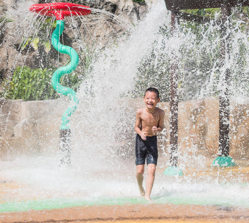 Asian child little boy having fun to play with water in park fountain in summer time stock photos
