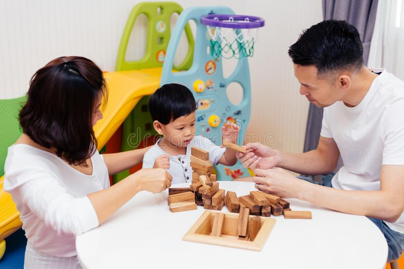 Asian child and parents playing with wooden blocks in the room at home. A kind of educational toys for preschool and kindergarten stock image