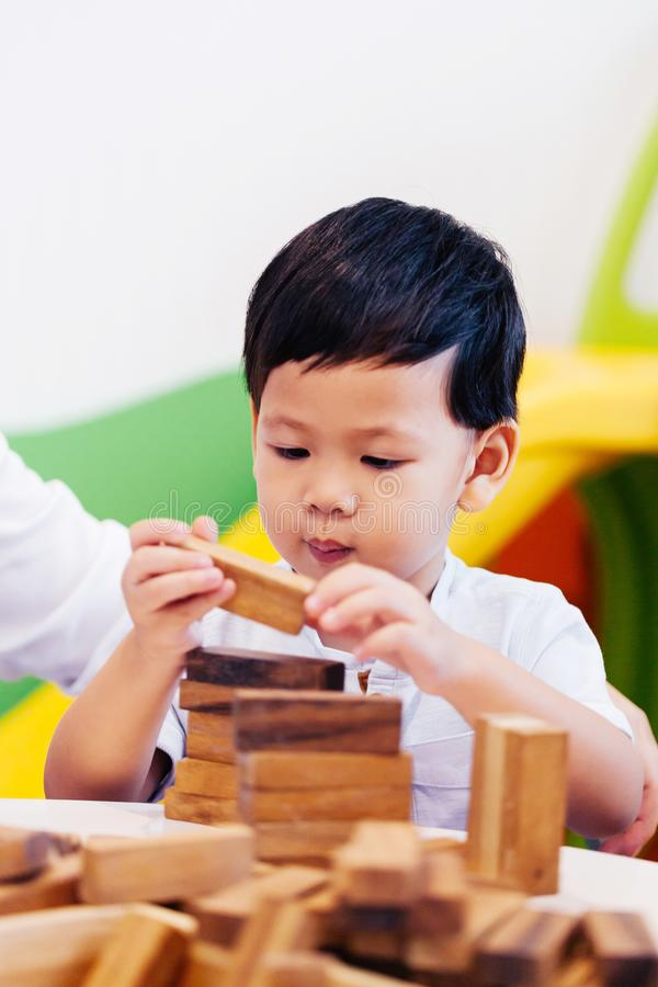 Asian child playing with wooden blocks in the room at home. A kind of educational toys for preschool and kindergarten kids stock photography