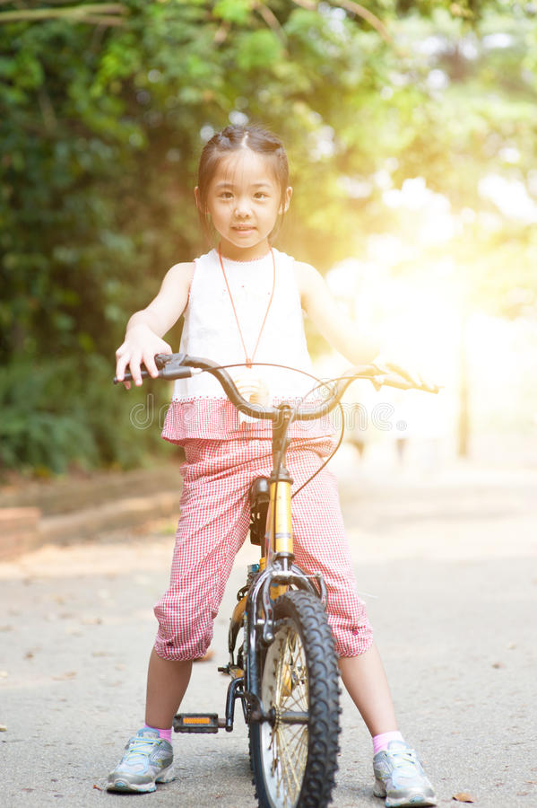 Asian child riding bikes outdoor. royalty free stock photography