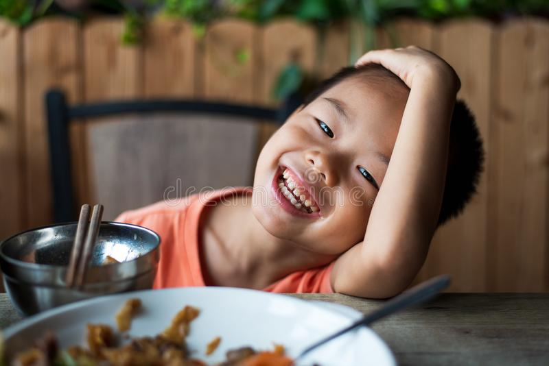 Asian child smiling at the restaurant. While having a meal, kid, eating, portrait, food, small, lunch, thai, chinese, chopsticks, 4, ethnicity, dish, hungry royalty free stock photos