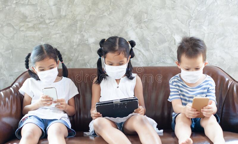 Asian children boy and girls wearing protection mask playing on the smartphone together at home quarantine from the coronavirus. Covid-19 and air pollution pm2 royalty free stock photo