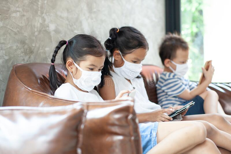 Asian children boy and girls wearing protection mask playing on the smartphone together at home quarantine from the coronavirus. Covid-19 and air pollution pm2 stock image