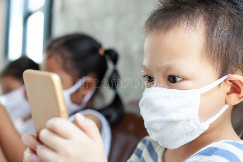 Asian children boy and girls wearing protection mask playing on the smartphone together at home quarantine from the coronavirus. Covid-19 and air pollution pm2 royalty free stock photography