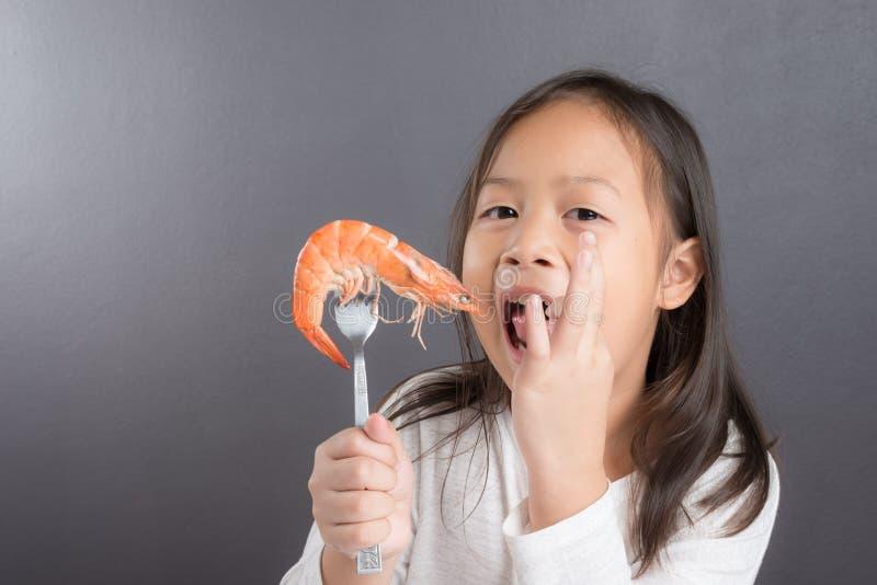 Asian children cute or kid girl eating shrimp stock photo