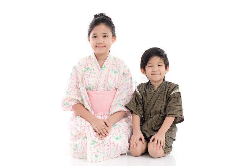 Asian children in Japanese Traditional Dress sitting. On white background isolated stock image