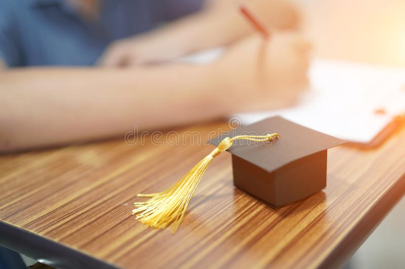 Asian children kid write answer in a quiz examination test study learn with graduation gap hat on wooden table in school. royalty free stock photography