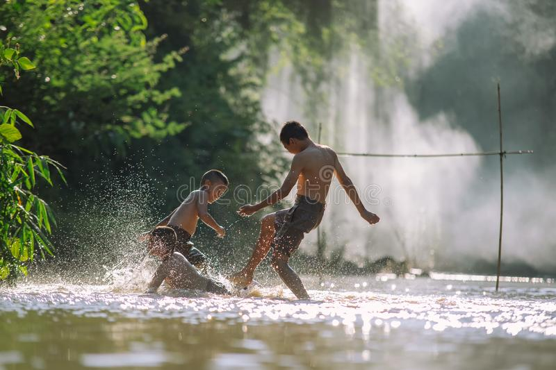 Asian children play soccer in the river,Sport plays an important stock image