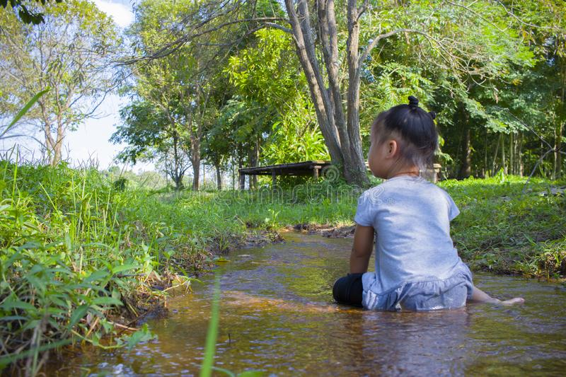 Asian Children playing  barefoot in stream water, catch a fish play mud and sand. High resolution image gallery stock photography