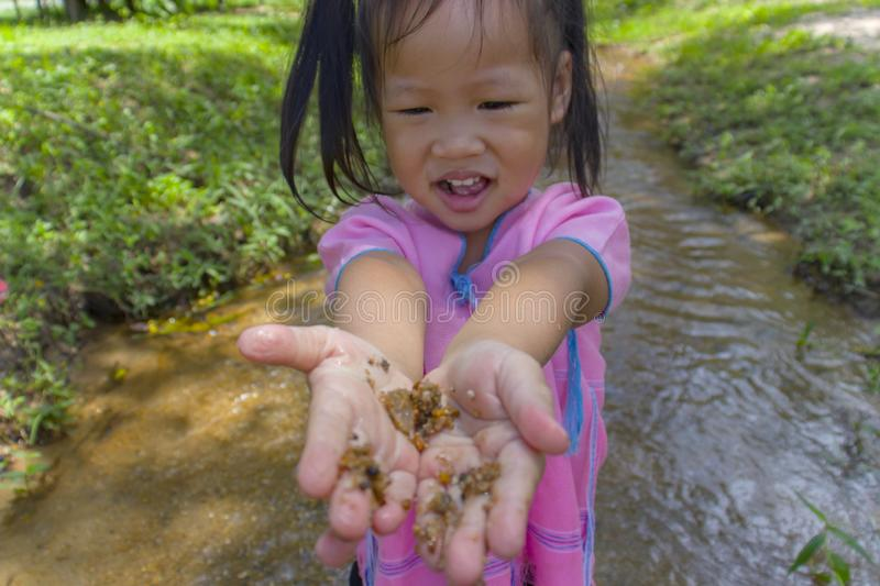 Asian Children playing  barefoot in stream water, play mud and sand. High resolution image gallery royalty free stock photography