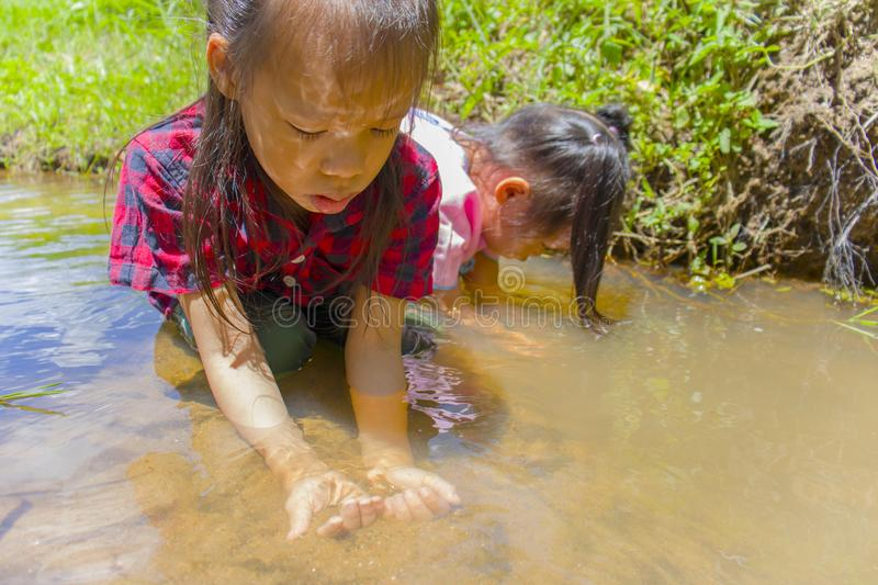 Asian Children playing  barefoot in stream water, play mud and sand. High resolution image gallery royalty free stock photo