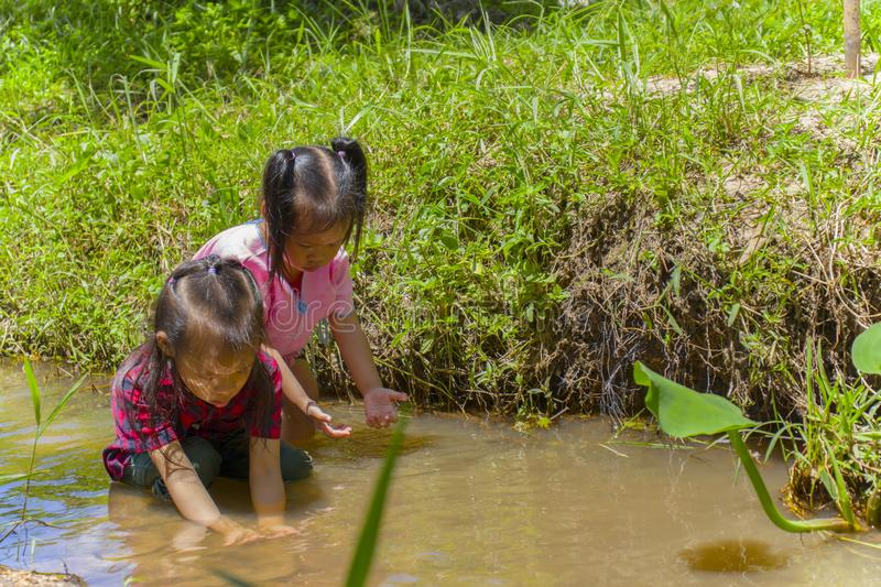 Asian Children playing  barefoot in stream water, play mud and sand. High resolution image gallery stock image
